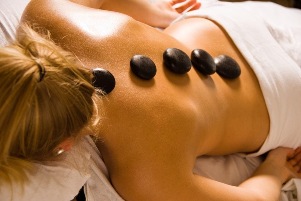 blond woman at a day spa with hot stones